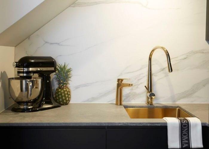 Billi Brass XL next to sink with stone splashback