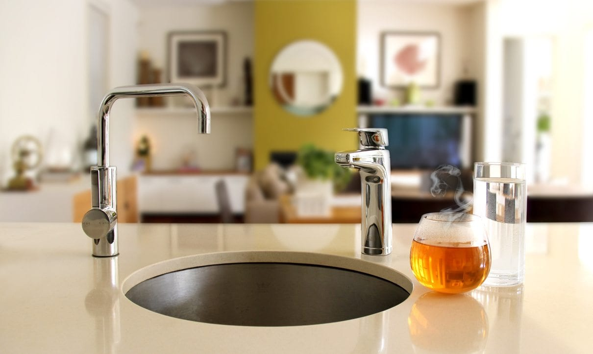 Bill Chrome XL dispenser on kitchen bench with cup of tea and glass of cold water