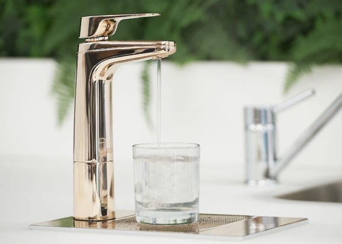 Billi XL Rose Gold dispenser on riser and font with glass of water