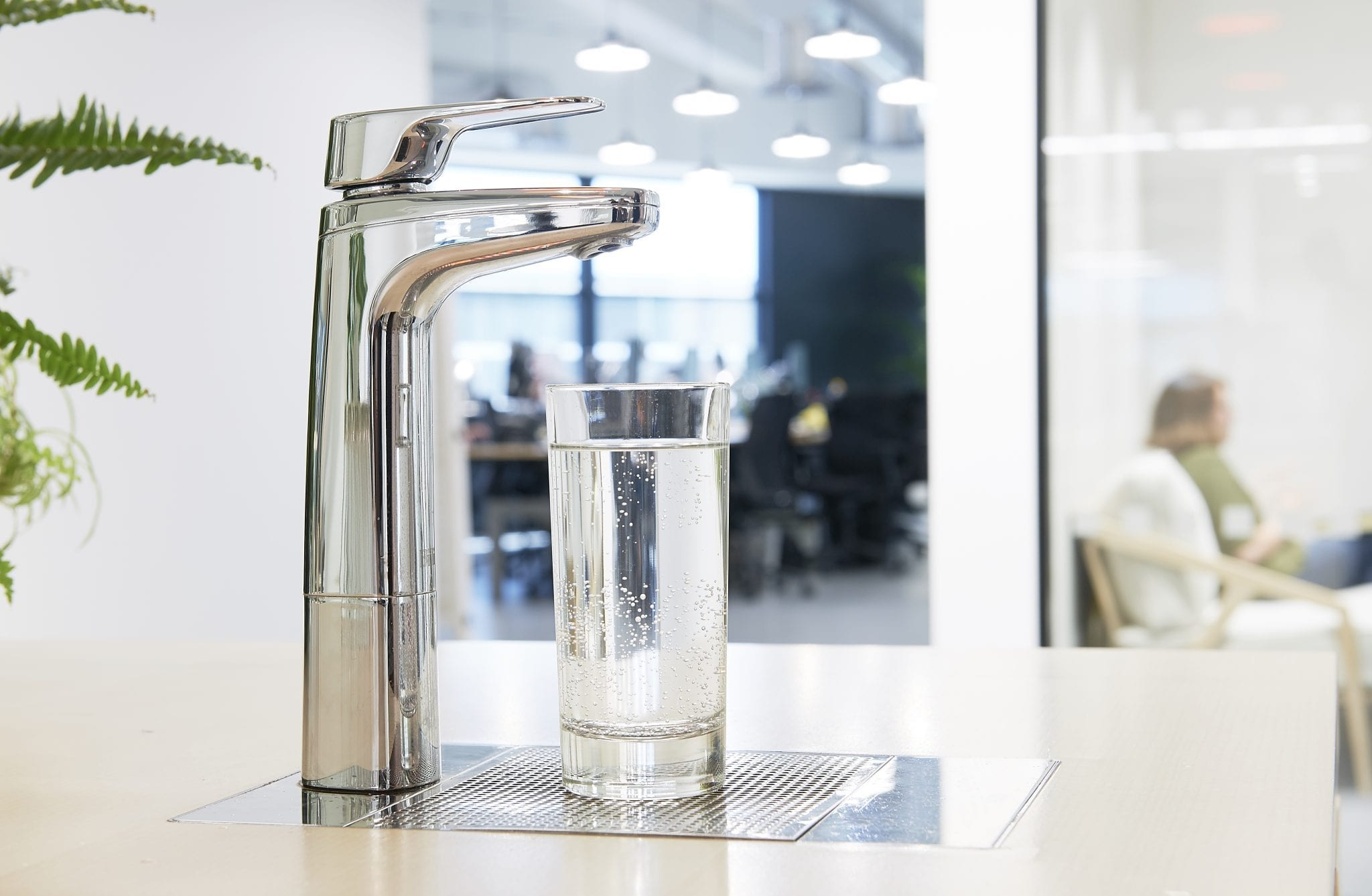 Chrome XL dispenser on riser and font with glass of sparkling water